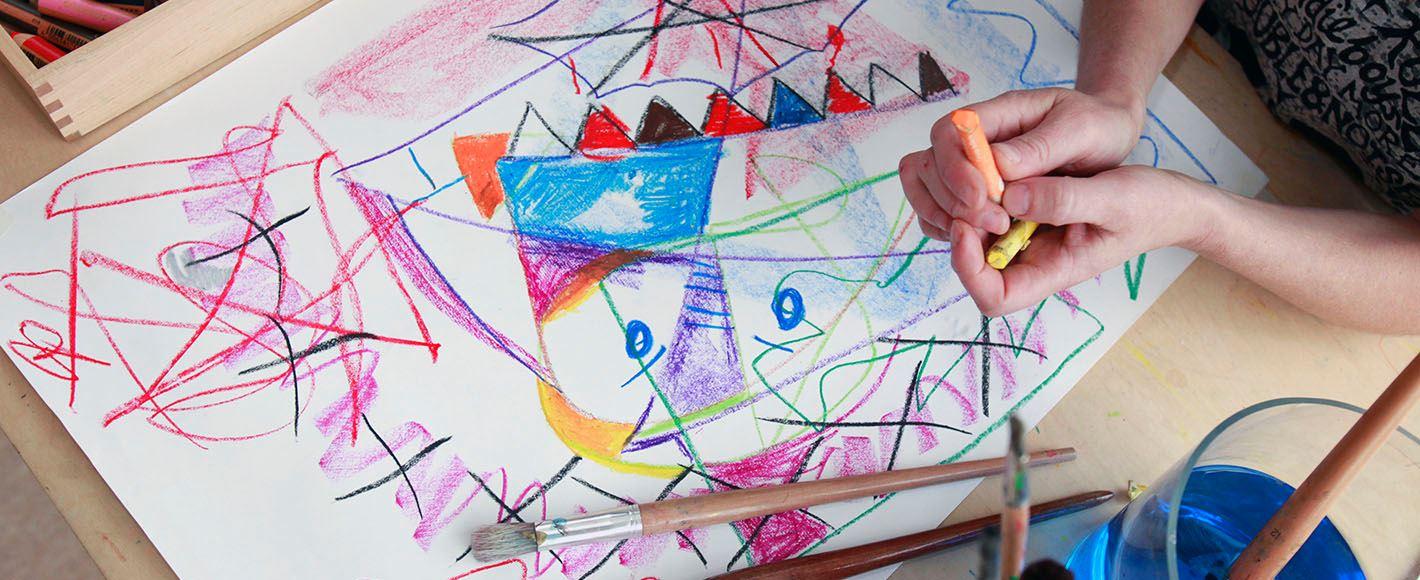 Kind maakt kleurrijke kindertekening voor de cursus Kindertekeningen analyseren