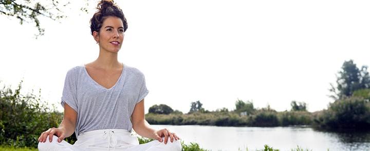 Vrouw doet meditatie oefening in de buitenlucht bij cursus Mindfulness