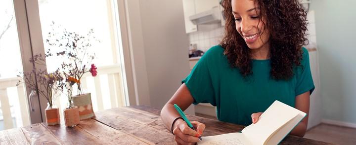 Vrouw schrijft aan tafel tijdens de cursus Therapeutisch schrijven