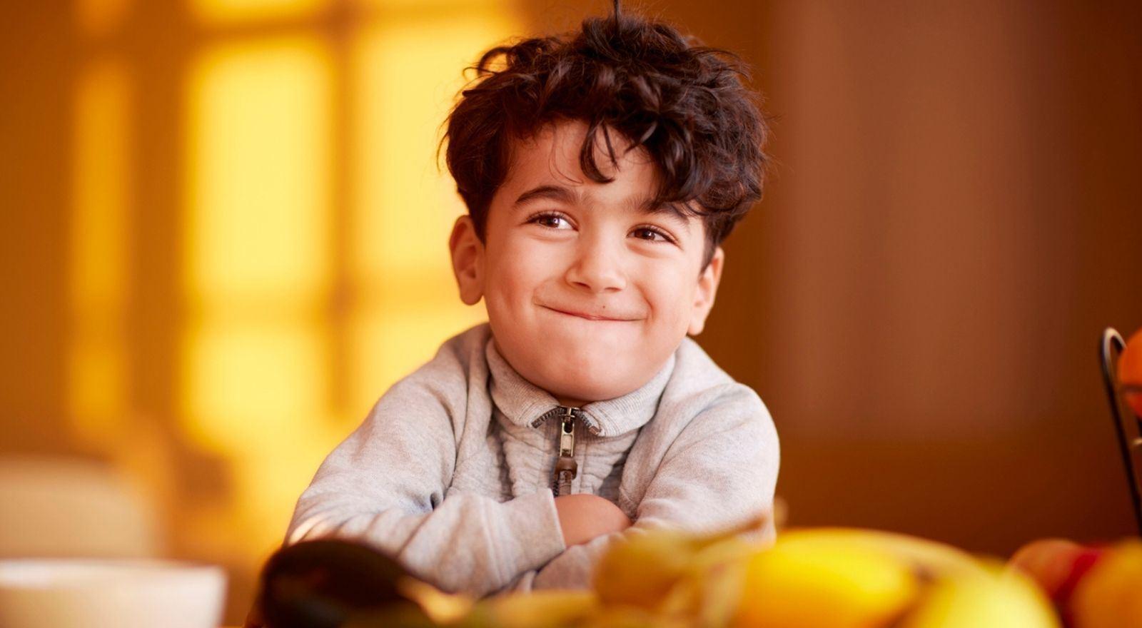 Klein jongetje kijkt met zelfvertrouwen door de opleiding zelfvertrouwen voor kinderen