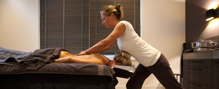Masseur aan het werk in massagesalon na cursus Holistische massage