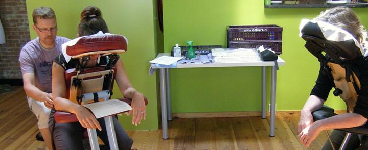 Masseur geeft cliënt een massage bij de cursus Stoelmassage